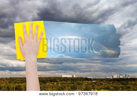 Hand Deletes Gray Clouds Over City By Yellow Cloth