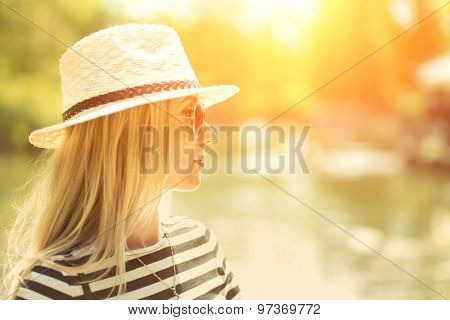 Portrait of blond woman in white hat and sunglasses on the lake background.