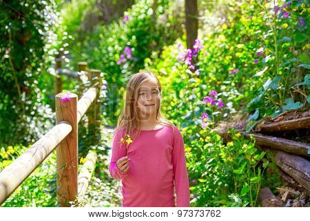 kid girl in spring track in Cuenca forest of Spain with wooden fence