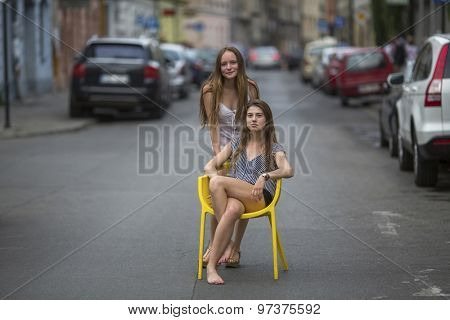 Cute adolescent girls sitting on a chair in the middle of the streets of the old town.