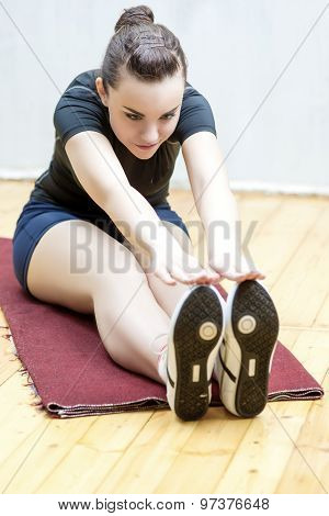 Sport And Fitness Ideas And Concepts. Portrait Of Happy Young Woman Doing Stretching Exercise In Gym