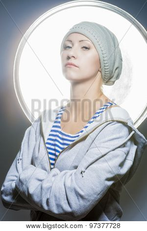 Fashion Portrait Of Proudly Looking Young Caucasian Female In Warm Hat Wearing Hoody Jacket. Against