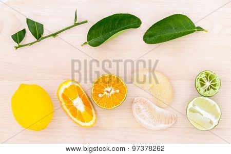 Mixed Citruses Fruit Oranges, Pomelo , Lemon And Lime On Wooden Background With Orange Leaf.