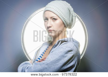 Fashion Shot Of Thinking Caucasian Blond Female In Warm Hat And Wearing Hoody. Posing Against Studio