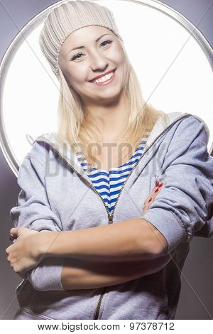 Portrait Of Smiling Positive Caucasian Blond Female Posing Against Studio Environment.