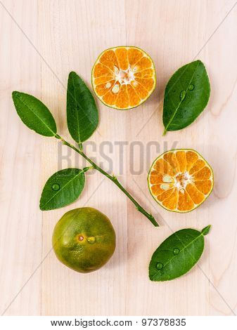 Fresh Oranges And Orange Slice On Wooden Background With Orange Leaf.