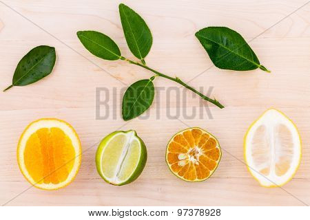Mixed Citruses Fruit Oranges, Lemon And Lime On Wooden Background With Orange Leaf.