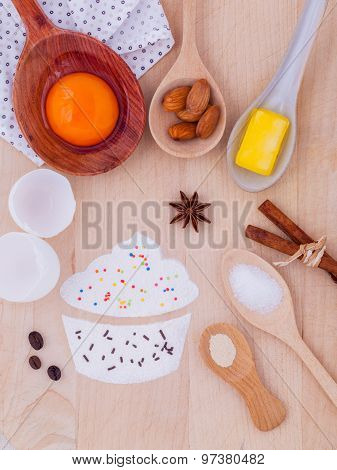 The Ingredients Of Cup Cake And The Shape Of Cup Cake With Topping On Wooden Table .
