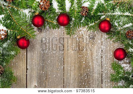 Snow Covered Fir Branches With Red Ornaments And Cones On Rustic Wooden Boards