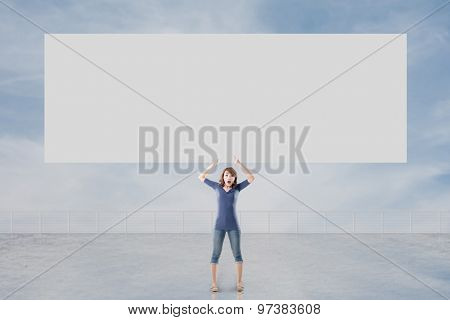 Woman holding blank board standing against the sky.
