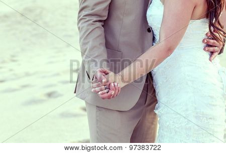 Bride And Groom's Hands With Wedding Rings On Tropical Beach.