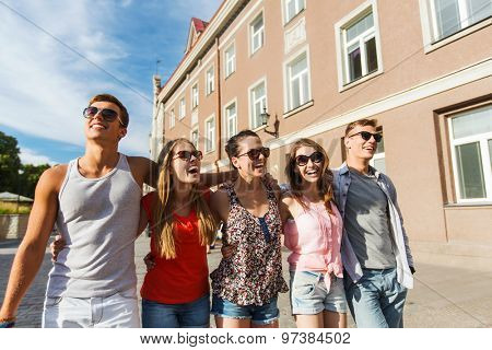friendship, travel, tourism, summer vacation and people concept - group of smiling teenagers walking in city