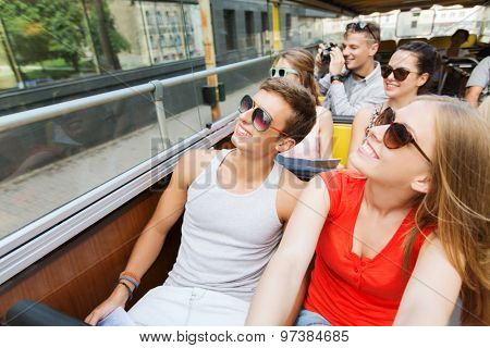 travel, tourism, summer vacation, sightseeing and people concept - group of smiling teenage friends in sunglasses traveling by tour bus