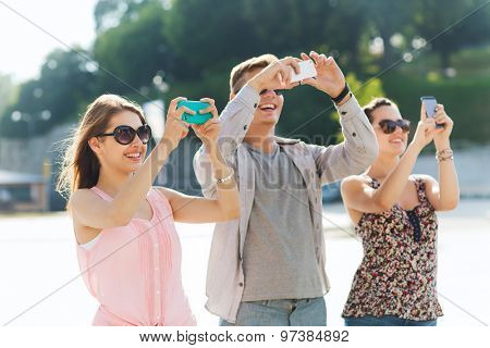 friendship, leisure, summer, technology and people concept - group of smiling friends with smartphone taking picture outdoors