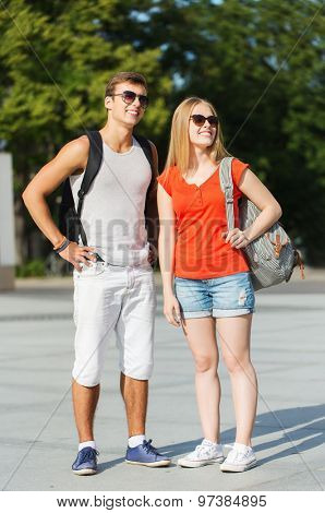 travel, summer vacation, tourism and friendship concept - smiling couple with backpacks in city