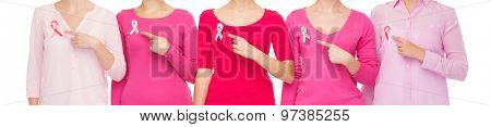 healthcare, people, gesture and medicine concept - close up of women in blank shirts pointing fingers to pink breast cancer awareness ribbons over white background