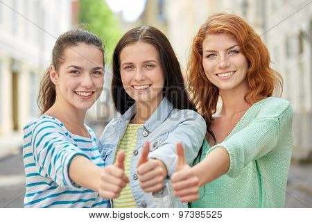 vacation, weekend, leisure and friendship concept - smiling happy young women or teenage girls showing thumbs up on city street