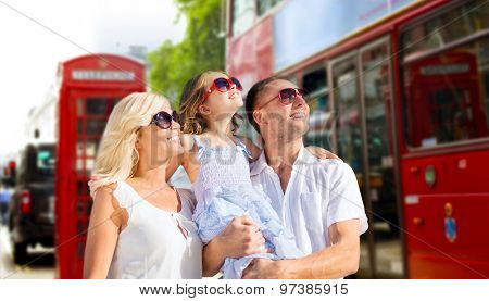 summer holidays, travel, tourism and people concept - happy family in sunglasses looking up over london city street background