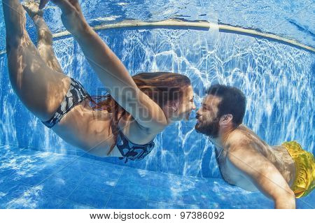 Positive Couple Swimming Underwater In Outdoor Pool