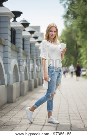 stylish woman drinking coffee to go in a city street