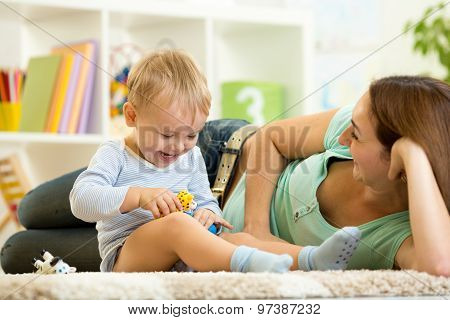 happy child holds animal toy playing with mom in nursery