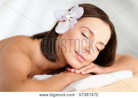 health, beauty, resort and relaxation concept - beautiful woman with flower in her hair in spa salon lying on the massage desk