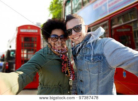 tourism, travel, people, leisure and technology concept - happy teenage international couple taking selfie over london city street background