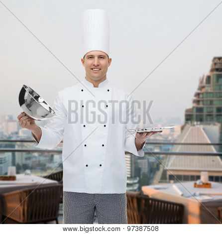 cooking, profession and people concept - happy male chef cook opening cloche cover over city restaurant lounge background