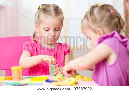 children girls play with colorful clay