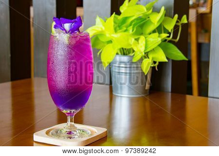 Juice of Butterfly pea with lemon and ice in glass on wooden table. Herb drink for refreshment.