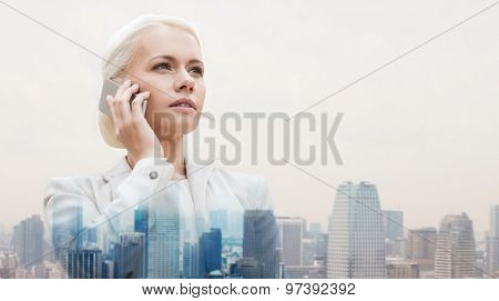business, technology, communication and people concept - serious businesswoman with smartphone talking over city background