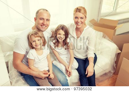 family, children, accommodation and home concept - smiling parents and two little girls moving into new home