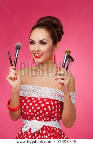 Smiling Woman with makeup brushes. She is standing against a pink background.