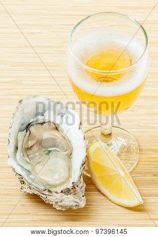Fresh Oysters With Lemon And A Glass Of Wine On A Wooden Table .