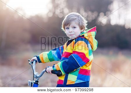 Kid Boy In Safety Helmet And Colorful Raincoat Riding Bike, Outd