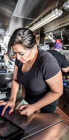 stock photo of food truck  - Female cashier with money on busy food truck - JPG