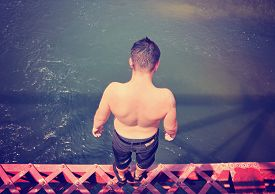 foto of trestle bridge  -  a boy getting read to jump off an old train trestle bridge into a river on a hot summer day toned with a retro vintage instagram filter app or action effect - JPG