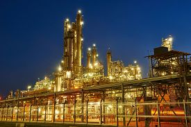 stock photo of refinery  - Oil refinery plant of petroleum or petrochemical industry production at sunset - JPG
