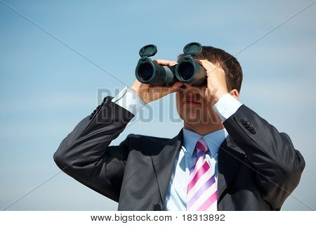 Portrait of confident man in suit observing through binoculars somewhere outside