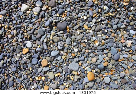 Smoothed Pebbles On The Beach By The Ocean