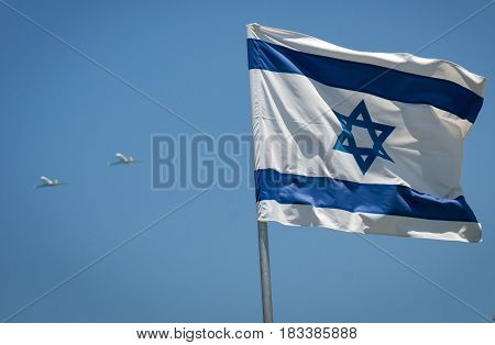 Combat planes flying over Tel Aviv seaside during the Independence day air parade with the flag of Israel in the front. Israel, May 12, 2016. Israel Independence Day stock image.