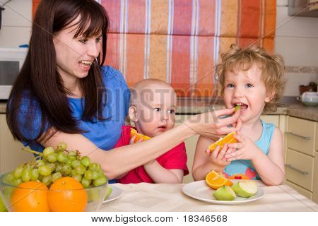 Beautiful happy mum with children eat fruiton kitchen