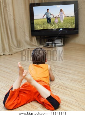 Child watching TV, laying on floor