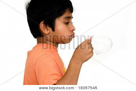 An handsome Indian kid blowing bubbles and having fun