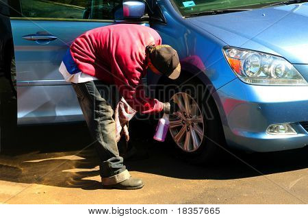 An young man washing the car wheels manually