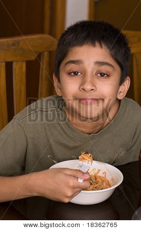 Handsome Indian kid happy eating noodles
