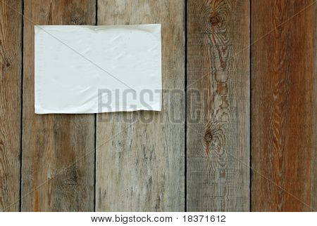 sheet of paper glued on wooden wall