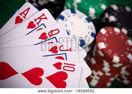 Cards with poker arrangement and poker chips in the background.