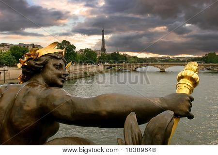 View on Seine river and Eiffel Tower through the sculpture on Alexander III bridge in Paris, France.
