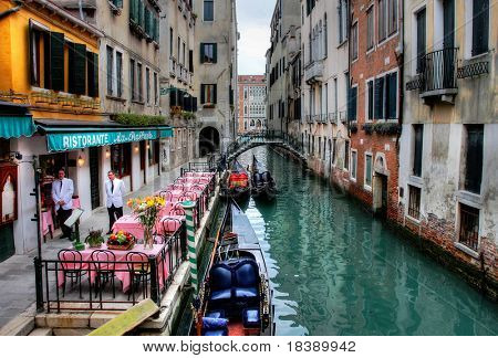 Small restaurant on venetian canal among old houses in Venice, Italy.